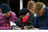 Racegoers study the race card during Bathwick Tyres Reduced Admission Race Day at Salisbury Racecourse on 9th October 2017
