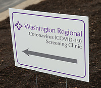 A sign stands Tuesday, March 17, 2020, to mark the entrance of a screening clinic operated by Washington Regional Medical Center at 3318 N. Northhills Blvd. in Fayetteville. Visit nwaonline.com/200318Daily/ for today's photo gallery.<br /> (NWA Democrat-Gazette/Andy Shupe)