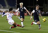 BOCA RATON, FL - DECEMBER 15, 2012: Megan Rapinoe (15) and Kelley O'Hara (5) of the USA WNT watch a cross from Ren Guixin (23) of China WNT during an international friendly match at FAU Stadium, in Boca Raton, Florida, on Saturday, December 15, 2012. USA won 4-1.