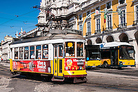 A typical streetcar (trolley) exiting the Commerce Square (Praca do Comercio) with modern buses in background, Lisbon, Portugal. Although Lisbon has a modern fleet of trams, climbing the steep hills and narrow streets of Lisbon is mostly done in small streetcars, that remain faithful to their style since their first uses in the city, including even the wooden benches and driving system inside.