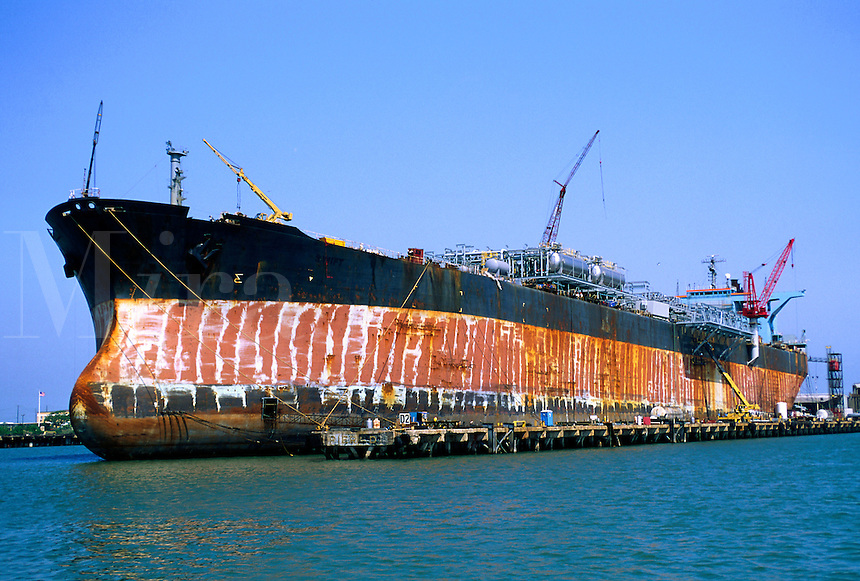 A cargo ship in drydock for repairs, maintenance and refitting.