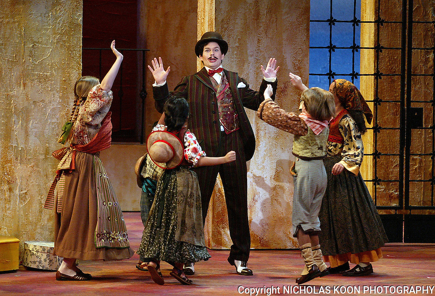 2002 - BARBER OF SEVILLE - Figaro (John Packard) amuses the local kids in Opera pacific's production of The Barber of Seville.