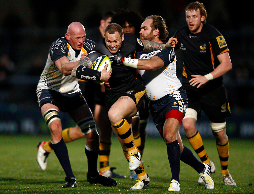Photo: Richard Lane/Richard Lane Photography. London Wasps v Worcester Warriors. LV= Cup. 18/11/2012. Wasps' Lee Thomas is tackled by Warriors' Craig Gillies and Andy Goode.