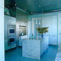 In the kitchen the splashback behind the stove is composed of stainless steel tiles, while designer cabinets and integrated appliances create a contemporary look