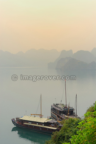 Asia, Vietnam, Halong Bay. Tourist junks within the mystic landscape of the Halong Bay. Designated a UNESCO World Heritage Site in 1994, the sensational Halong Bay is spread across 1.500 sq km, with more than 2.000 pinnacle shaped limestone and dolomite outcrops scattered across it. The impression is a labyrinthine seascape of bizarrly shaped outcrops, isolated caves, and sandy coves.