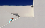 Woman climbing steps blue sky and white wall