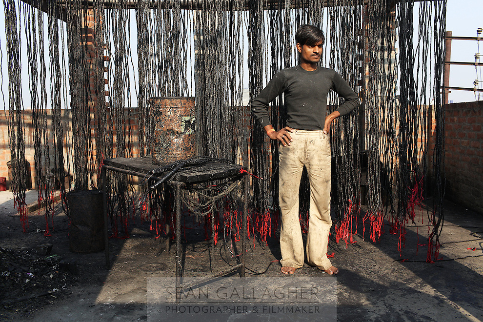 A worker stands barefoot next to a collection of leather whips which will be exported to the USA. The city of Kanpur produces a wide variety of leather products that will all be exported to the West.