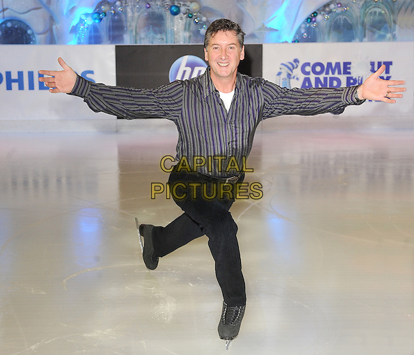 ROBIN COUSINS .opens the new Ice Rink at Westfield Shopping Centre, London, England, UK, .12th November 2010..full length skating grey gray black trousers striped shirt arms outstretched posing photocall skates skater .CAP/BEL.©Tom Belcher/Capital Pictures.