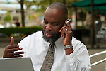 African American man with laptop and talking on cell phone