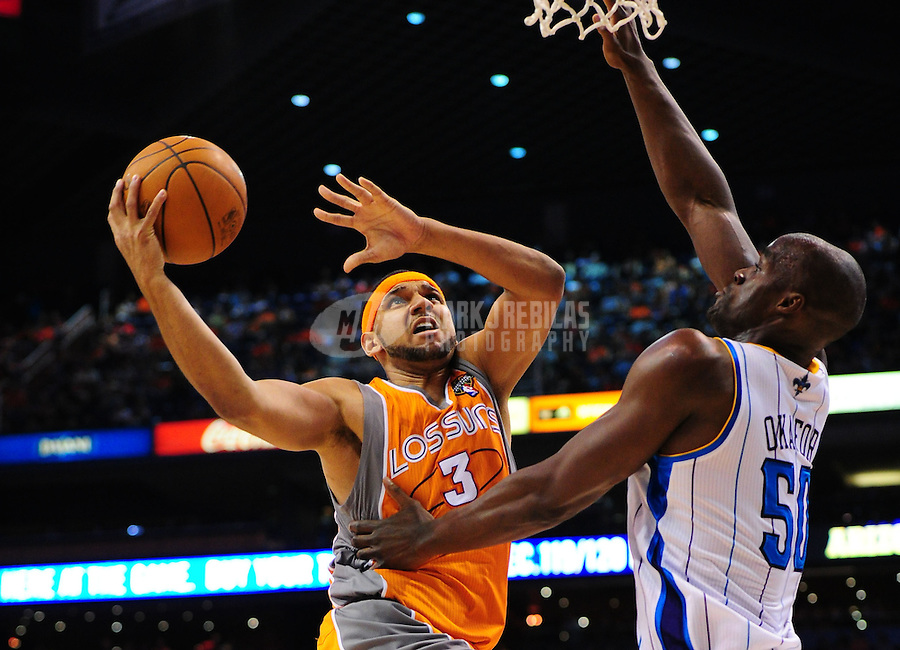Mar. 25, 2011; Phoenix, AZ, USA; Phoenix Suns forward (3) Jared Dudley takes a shot under pressure from New Orleans Hornets center (50) Emeka Okafor in the second half at the US Airways Center. The Hornets defeated the Suns 106-100. Mandatory Credit: Mark J. Rebilas-.