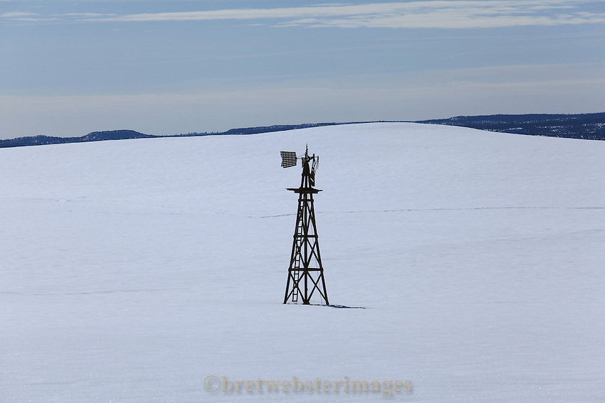 A lonely, small windmill stands sentry on a snow field near Zion National Park.