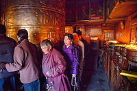 Buddhist pilgrims in Tibet turn a giant prayer wheel inside a small temple n the Barkhor circuit
