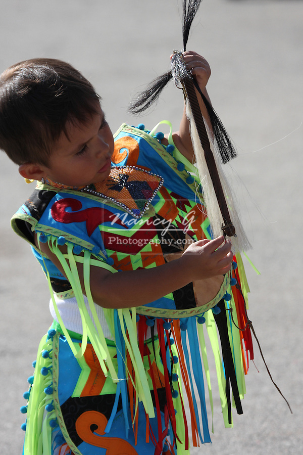 A young Native American Indian boy holding a horse hair whip in a fancy dancing outfit at a Pow Wow at the Milwaukee Lakefront Indian Summer Festival, Wisconsin