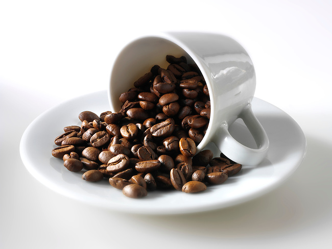 Fresh whole coffee beans in a cofee cup against a white background