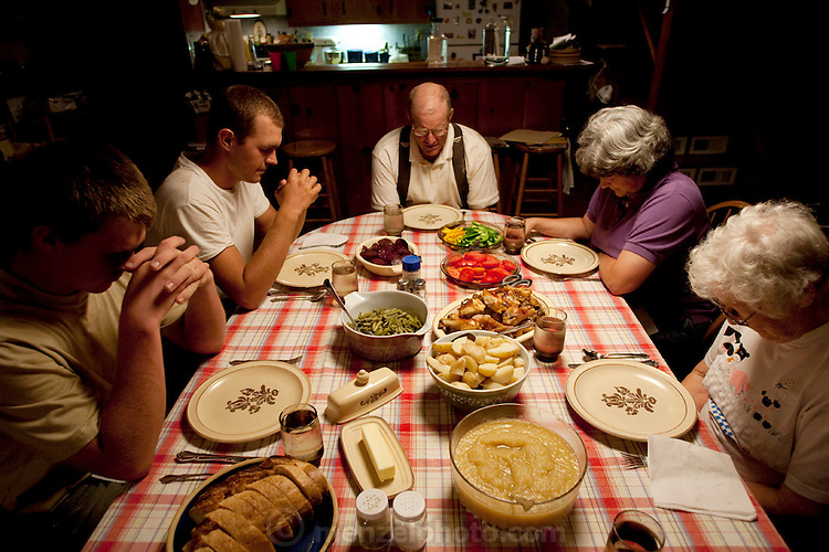 A prayer and then supper at Joel and Teresa Salatin's eighteenth-century farmhouse in Shenandoah, Virginia. (From the book What I Eat: Around the World in 80 Diets.) Joel (center) and Teresa (at his left) are joined by Joel's mother, Lucille, who lives on the farm, and farm apprentices Andy Wendt and Ben Beichler. Supper tonight is Teresa's honey-baked Polyface Farms chicken, which ?can't be served without her homemade applesauce,? says Joel. In addition, there are buttered potatoes, garden-fresh green beans with cured bacon, buttered beets, and sliced fresh garden vegetables. But Joel's favorite meal of the day? Breakfast! ?Aw man, pancakes, eggs, and sausage or bacon!?