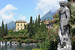 A view of Varenna, a town on Lake Como, Italy with a statue in the Villa Monastero gardens in the foreground.
