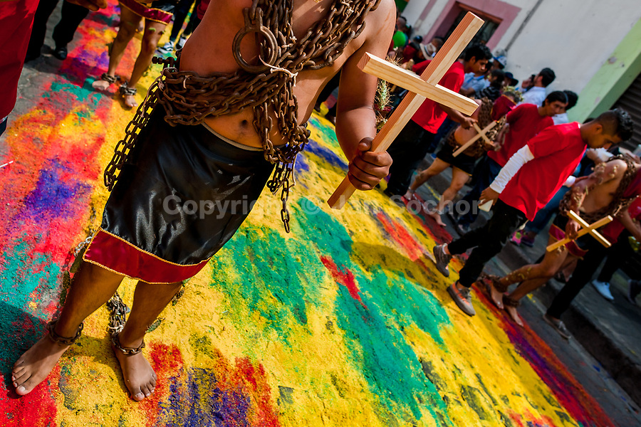 A chained penitent, wearing cactus spines stuck to his body and holding a wooden cross, walks on a colorful sawdust carpet during the Holy week procession in Atlixco, Mexico, 30 March 2018. Every year on Good Friday, dozens of anonymous men of all ages voluntarily undergo pain and suffering during the religious procession of the 'Engrillados' (the Shackled ones) in Puebla state, central Mexico. Wearing heavy chains on their shoulders covered with prickling cacti while being burned by the hot midday sun, they recall Jesus Christ's death by crucifixion and demonstrate their religiosity and faith.