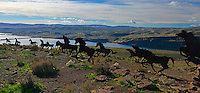 "Wide view of steel sculpture group formally titled ""Grandfather cuts loose the ponies"", also known as ""Wild Horses Monument"" on plateau above Interstate Highway 90 and Columbia River in Washington State."