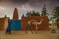 AGADEZ, NIGER &mdash; <br /> Tuareg camel traders walk past the Agadez Mosque. Originally built in 1515 this mosque was restored in 1844 and is a central landmark in this city. <br /> Agadez, is the largest city in central Niger with an estimated population of over 120,000 people. This city, comprised mainly of one-story mud structures, is situated on the southern outskirts of the Sahara desert and has been an important trade center for centuries. Tuareg and Berber tribes have traveled the many commercial routes that run through the desert for more than a thousand years. Today, this city has become one of the largest human smuggling and drug trafficking routes in West Africa. Thousands of migrants attempting to reach Europe are smuggled through the Sahara desert to Libya, Algeria and Morocco in their attempts to reach Italy and Spain.