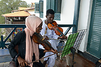 TANZANIA, Zanzibar, Stone town, Dhow countries music academy, girl and boy play violin on balcony