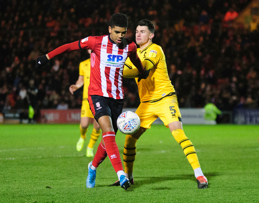 Lincoln City's Tyreece John-Jules vies for possession with Milton Keynes Dons' Regan Poole<br /> <br /> Photographer Andrew Vaughan/CameraSport<br /> <br /> The EFL Sky Bet League One - Lincoln City v Milton Keynes Dons - Tuesday 11th February 2020 - LNER Stadium - Lincoln<br /> <br /> World Copyright © 2020 CameraSport. All rights reserved. 43 Linden Ave. Countesthorpe. Leicester. England. LE8 5PG - Tel: +44 (0) 116 277 4147 - admin@camerasport.com - www.camerasport.com