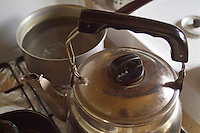 Pan fill of liquid and a teapot on a cooker stove.
