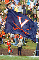 A cheerleader runs the Virginia flag.