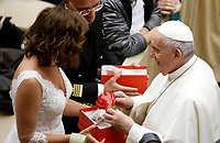 Pope Francis receives a present from a newlywed couple at the end of his weekly general audience in the Paul VI hall at the Vatican, January 22, 2020.<br />