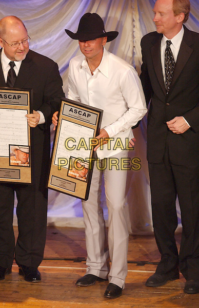 KENNY CHESNEY.First public appearance since his split from Renee as he accepts the prestigious ASCAP Voice of Music Award during the 2005 ASCAP Awards Show held at the Ryman Auditorium, Nashville, Tennessee..October 17th, 2005.Photo Credit: Laura Farr/AdMedia/Capital Pictures.Ref: LF/ADM.full length cowboy hat stetson white shirt grey gray trousers plaque.www.capitalpictures.com.sales@capitalpictures.com.© Capital Pictures.