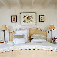 Framed seashell prints hang above the French bed with identical lamps either side