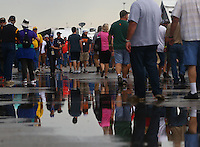 Apr 25, 2015; Baytown, TX, USA; NHRA fans reflect in a rain puddle as they walk through the pits during a rain delay to qualifying for the Spring Nationals at Royal Purple Raceway. Mandatory Credit: Mark J. Rebilas-