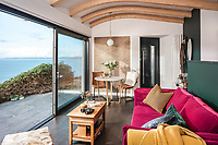 BNPS.co.uk (01202 558833)<br /> Pic: UniqueHomeStays/BNPS<br /> <br /> Pictured: There is a modern living area with large sliding doors that make the most of the 180 degree views.<br /> <br /> A couple who spent £450,000 on turning a 'rotting shed' into an exclusive seaside bolthole hope to recoup their money - by renting it out for £3,150 a week. <br /> <br /> Tracey Gilpin and Peter Burridge went out on a limb when they bought the 60-year-old wooden shack for a whopping £220,000.<br /> <br /> Despite its ramshackle condition, the cabin could command such a hefty asking price as it is located halfway up a cliff with stunning views of Whitsand Bay in Cornwall.<br /> <br /> But in order to make the coastal chalet a viable holiday let the couple had to demolish it and build a new one from scratch.
