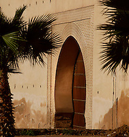 Entrance between Bab Mansour and the Royal Palace, Meknes, Morocco pictured on December 26, 2009. Palm trees flank the sunlit traditional archway in the stuccoed wall. The Bab Mansoor Gate, completed in 1732, is named after its architect. Meknes, one of Morocco's Imperial cities, was redeveloped under Sultan Ismail Moulay (1634-1727). It is a fortified city built from pise, or clay and straw, and was designed to be the political capital of Morocco, as opposed to Fez, the religious capital. Picture by Manuel Cohen