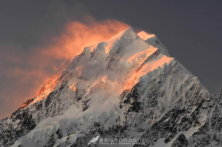Wind blown snow on the summit of Aoraki / Mt Cook is illuminated at sunset