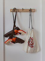 A pair of child's cowboy guns in holsters and a drawstring bag hang from a wooden peg rail.