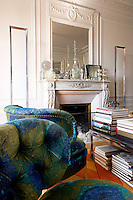 In the living room a matching pair of upholstered armchairs is placed next to a coffee table stacked with books