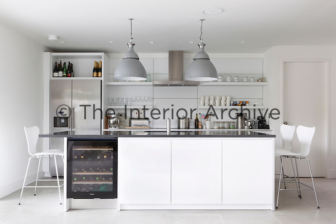 A well-equipped contemporary kitchen occupies one half of the open plan kitchen/dining area and centres around a kitchen island which doubles as a breakfast bar