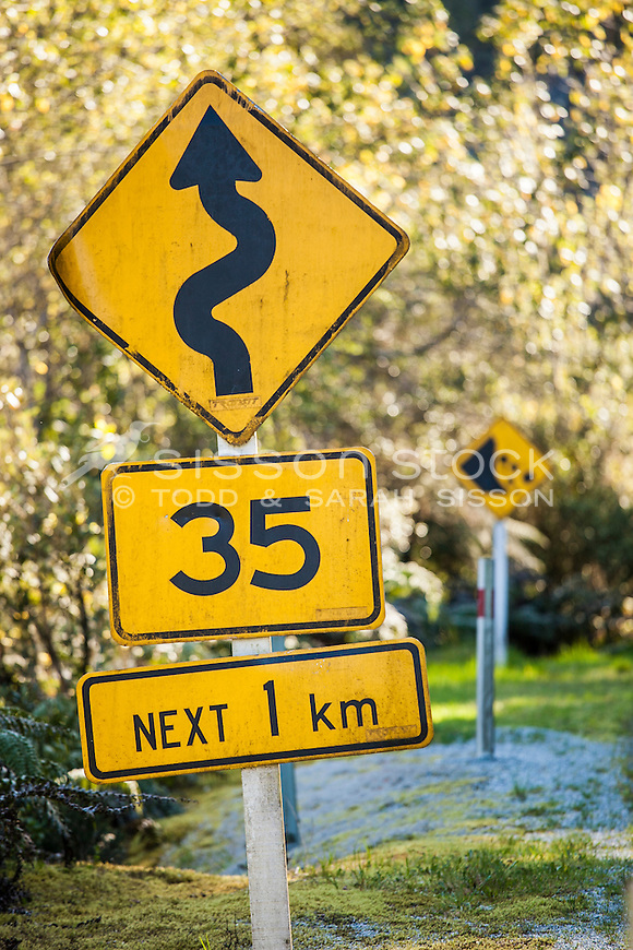 multiple road warning signs and speed advsisories (35kph), West Coast New Zealand.