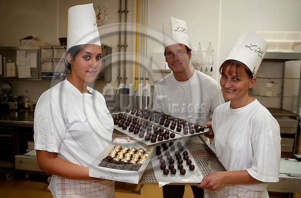 """VIENNA - AUSTRIA  14. AUGUST 2006 -- K.U.K Hofzuckerb?cker (kingly and imperially confectioner) - Nicole Heindel (left), Thomas Krappl and Veronika Nodj with Mozart Kugeln and other confect -- PHOTO: CHRISTIAN T. JOERGENSEN / EUP & IMAGES..This image is delivered according to terms set out in """"Terms - Prices & Terms"""". (Please see www.eup-images.com for more details)"""