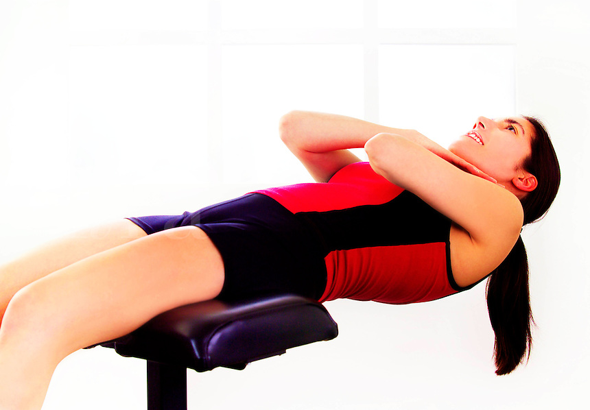 Beautiful female in her work out on a machine doing crunches.