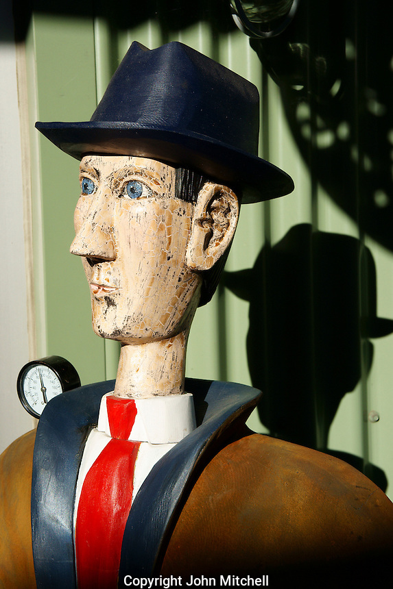 Humorous wooden carving of a skinny man in a black hat Granville Island, Vancouver, BC, Canada
