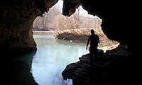 NWA Democrat-Gazette/DAVID GOTTSCHALK  Greg Adams, of Fayetteville, explores the ledge area above the water inside Cave Spring on the Current River in southeast Missouri.