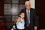 Palestinian President Mahmoud Abbas meets a nine-year-old Palestinian boy Waqas al-Saifi who lost his arm after being attacked by a bear in the Qalqiliya Zoo, in the West Bank city of Ramallah on May 26, 2017. Photo by Osama Falah