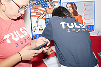 People wear campaign shirts as Democratic presidential candidate and Hawaii representative (D-HI 2nd) Tulsi Gabbard speaks at a campaign event at Weare Public Library in Weare, New Hampshire, on Thu., September 5, 2019.