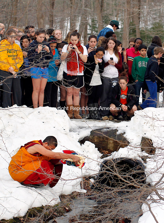 Middlebury, CT- 18, February 2011-021811CM03  A Tibetan Monk pours sand into a river on the Westover School campus in Middlebury Friday afternoon. The Monks, who were working on a sand mandala, finished the work, and lead a processional through the campus and out to this river.  The sand is said to bring the campus good luck.  Christopher Massa Republican-American