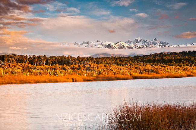 Sunset over Southern Alps mountains seen across Five Mile Lagoon near Okarito, Westland National Park, West Coast, South Westland, World Heritage Area, South Island, New Zealand