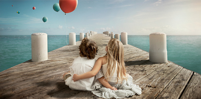 A girl and a boy sitting on a pier while watching balloons float away.