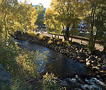 On a September evening fall color in cottonwood trees graces the Riverwalk which follows the Big Thompson River through downtown Estes Park, Colorado, Rocky Mountains