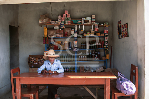 San Ignacio, Peru. Man wearing a wide-brimmed straw hat sitting at a table in a small roadside shop cum cafe with lopsided shelves selling soft drinks, chewing gum, toilet paper, sweets, torches, soap, biscuits, medicines, matches, toothpaste etc.