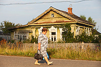 Novy Gorky, Ivanova Region, Russia, 05/08/2012..A woman walks past a traditional Russian wooden home in a settlement near Novy Gorky, some 200 miles east of Moscow.